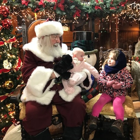 two children visiting Santa at The Brass Rooster hat shop