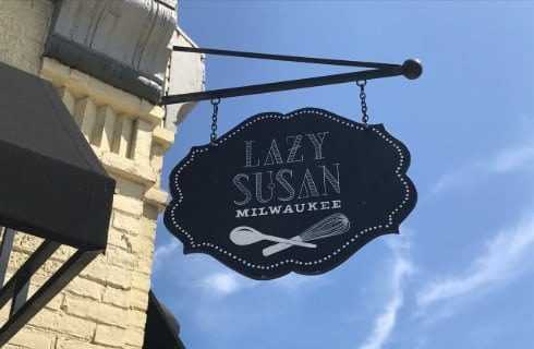 Painted brick building with a sign that says Lazy Susan Milwaukee.
