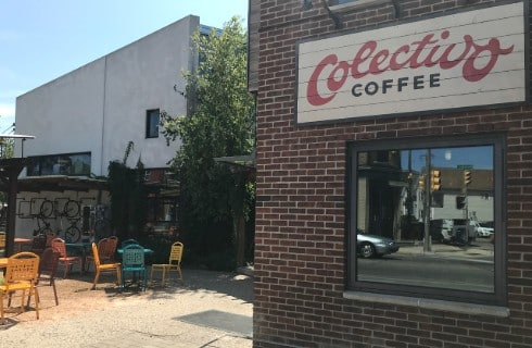 Patio with tables and chairs outside a brick building with sign that says Colectivo Coffee.