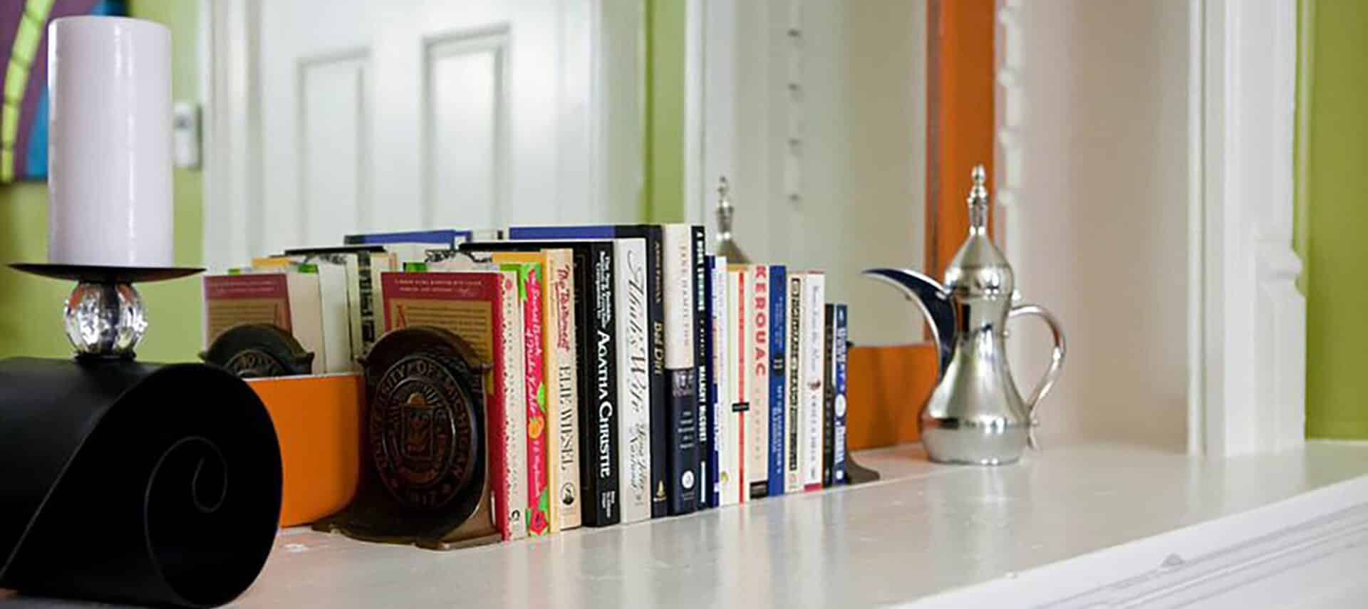 Row of books with brass bookends on a mantel in front of a mirror.