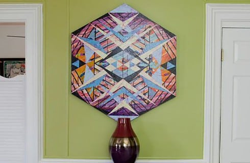 Decorative art vase on a table under an abstract tribal art piece.