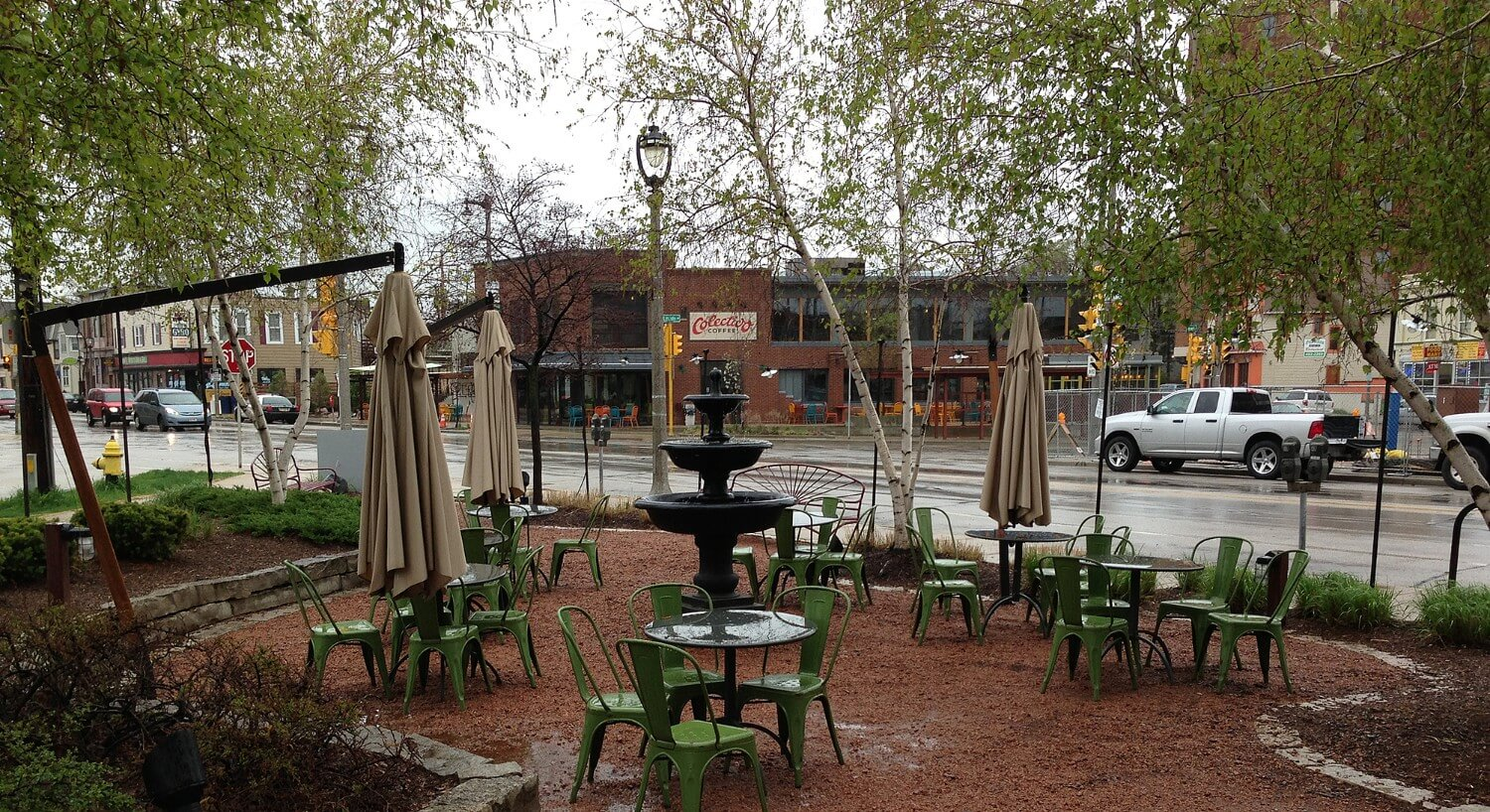 Seating area with green metal tables and chairs on a red gravel patio next to the street.