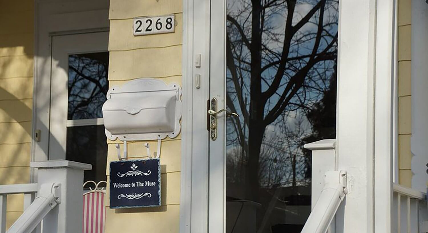 Front door of yellow house with white metal mailbox and sign that says, Welcome to The Muse.