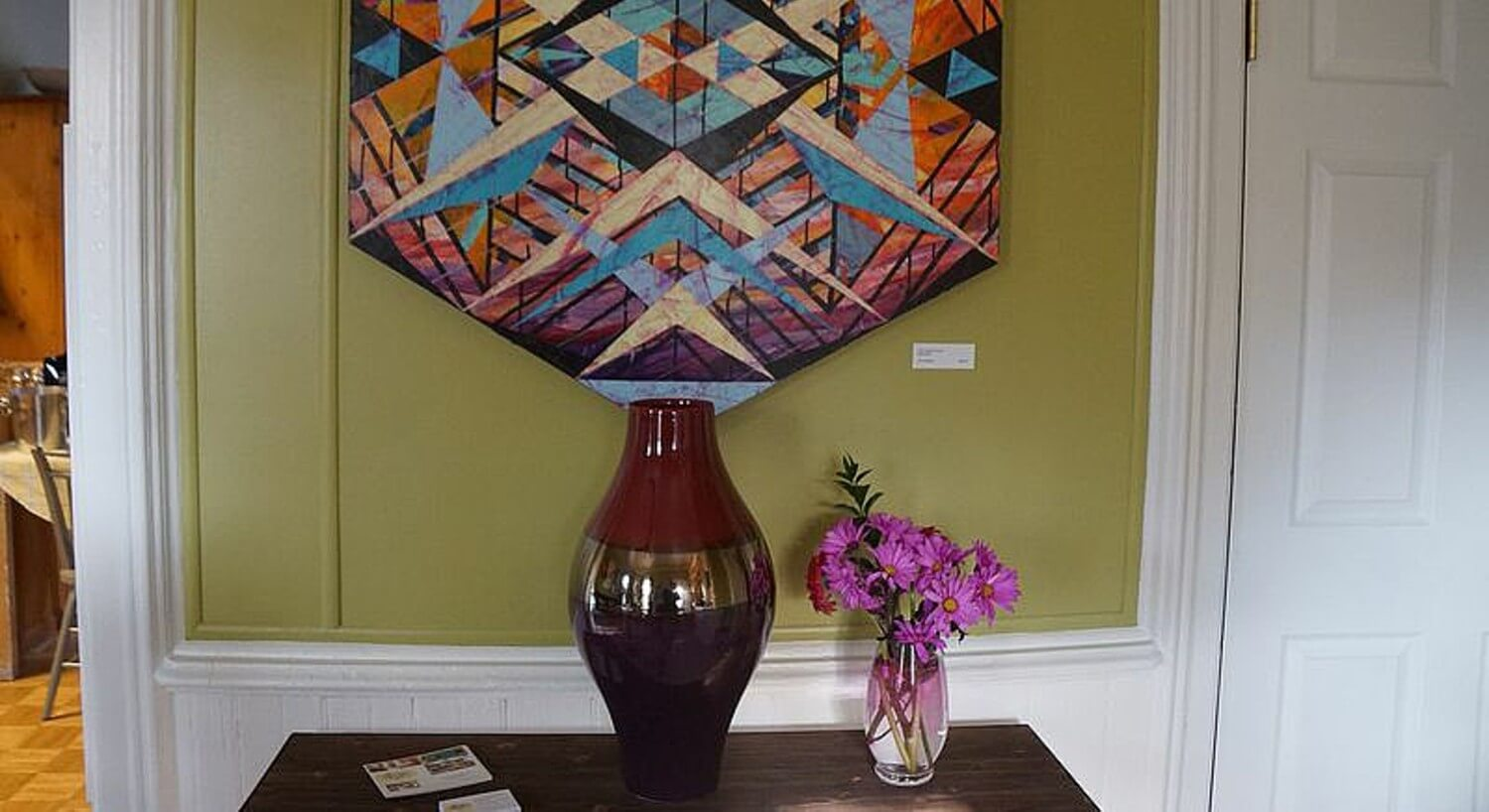 Decorative vase on wooden table under a modern art piece.