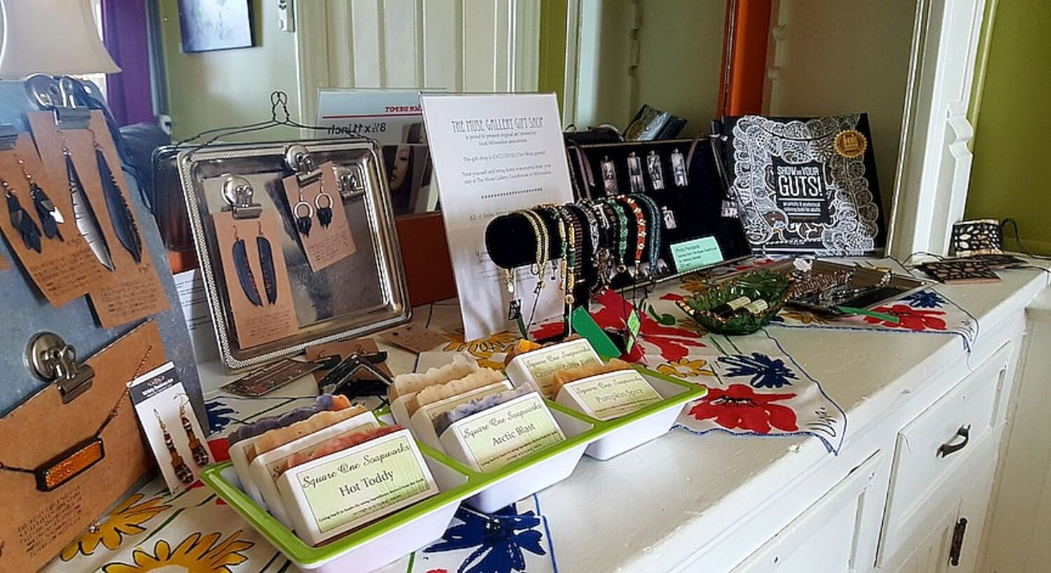 Table of wares for sale including soaps, jewelry and books.