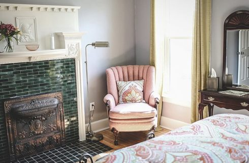 Tiled fireplace is the focal point of a bedroom with a bed, peach armchair and a vanity.