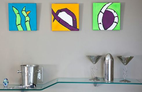 Bright abstract art pieces over a funky glass shelf holding silver cocktail items.