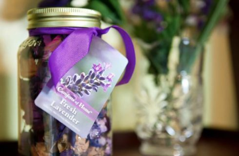 Mason jar full of fresh lavender popourri next to a vase with flowers.
