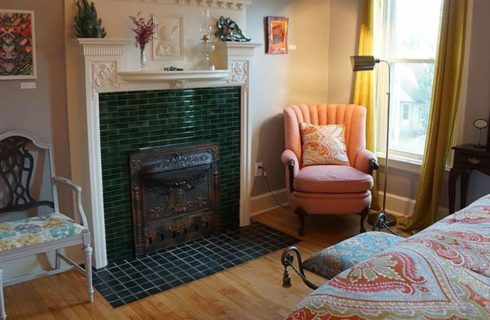 Tiled fireplace is the focal point of a bedroom with a bed, armchairs and a vanity.