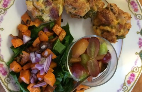 Roasted root vegetables with fruit salad and baked breakfast muffins on a china plate.