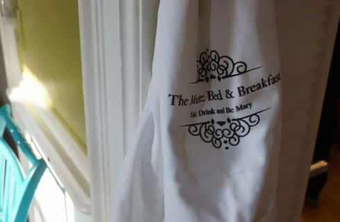 Flour sack towel hanging from wall with text: The Muse Bed & Breakfast Eat, Drink and Be Mary.