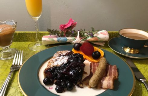 French toast with blueberry compote accompanied by sausage and bacon with coffee and orange juice.