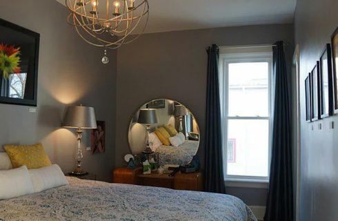 Bedroomw ith a queen bed, antique vanity and interesting light fixture.