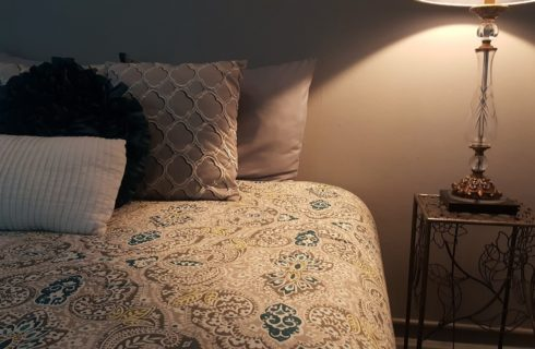 Paisley patterned spread on a bed next to a wire table with a lamp.
