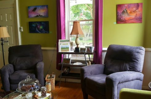 Two purple upholstered chairs in a lime green room sit beside a window with fuschia drapes.