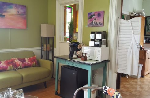Green sofa in a room with art on the walls and swinging louvered doors to a kitchen.