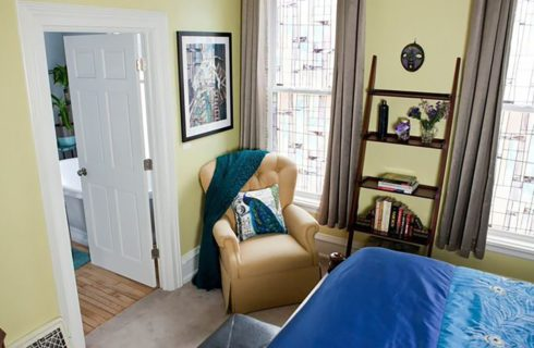 view from above of yellow bedroom with bed made up in blue and a wingback recliner.