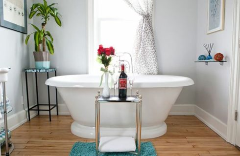 Bathroom in white with a soaking tub in front of a window with a patterned curtain.