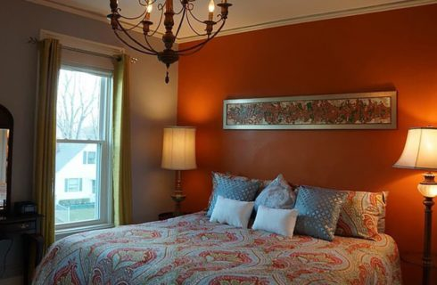 Guestroom with orange and blue walls with a queen bed and two nightstands with lamps.