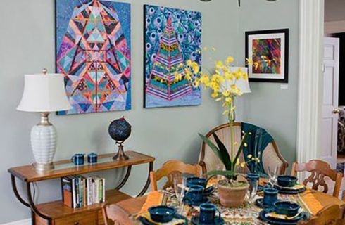 Original art pieces on the walls of a room with a table set for breakfast and console table.