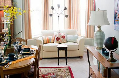 White sofa in front of a window with peach drapes in a room with a dining table and chairs.