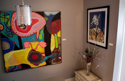 Original art pieces on the walls of a room with beige walls and a silver light fixture.