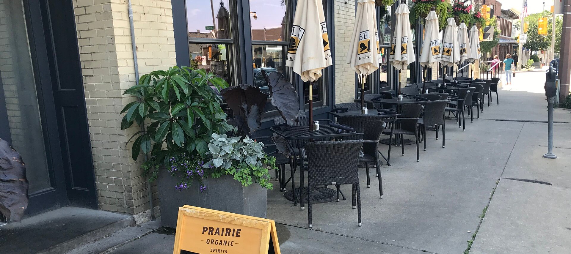 Black iron bistro tables and chairs set up outside a restaurant on a city street.
