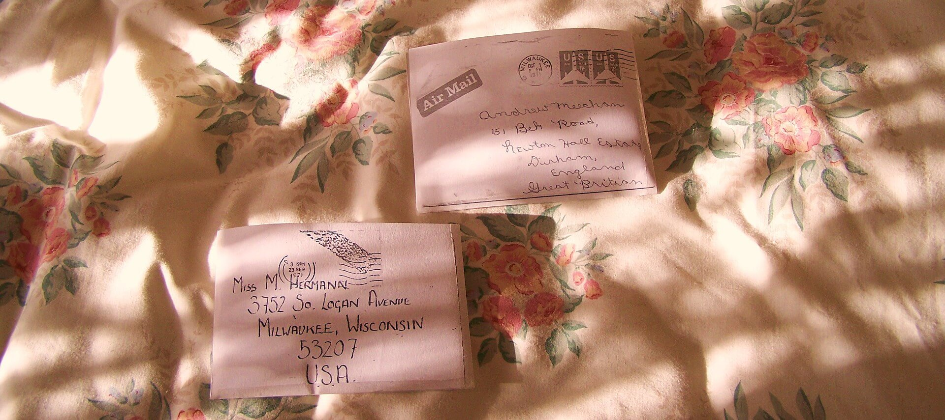 Two old letters with handwritten addresses on a cream and flowered blanket