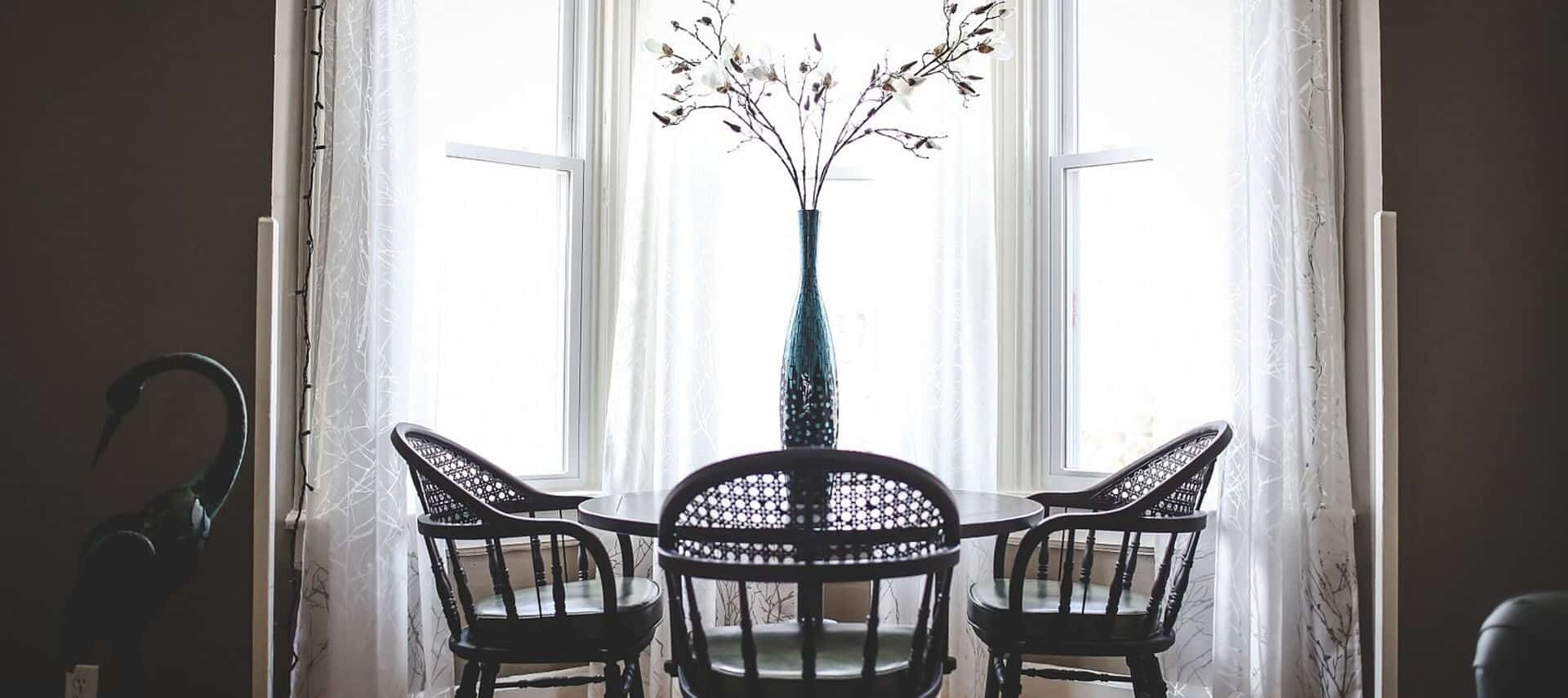 Small table and chairs set in front of a bow window with gauze curtains.