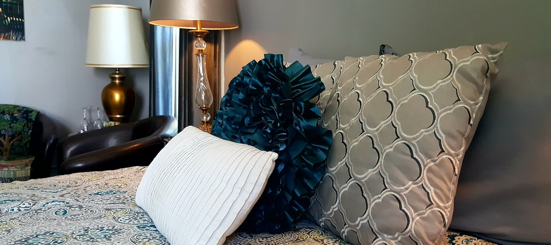 Bed made up with tan and teal paisley spread and decorative pillows next to a nightstand and leather club chair.