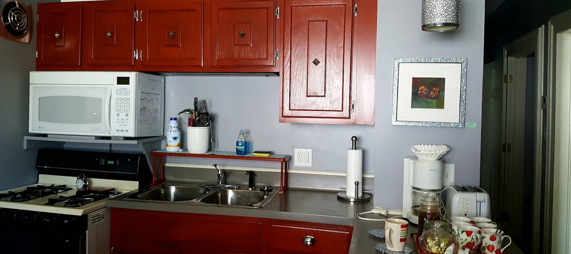 Kitchen with cherry cabinets, a gas stove and microwave and coffee station on the bar.