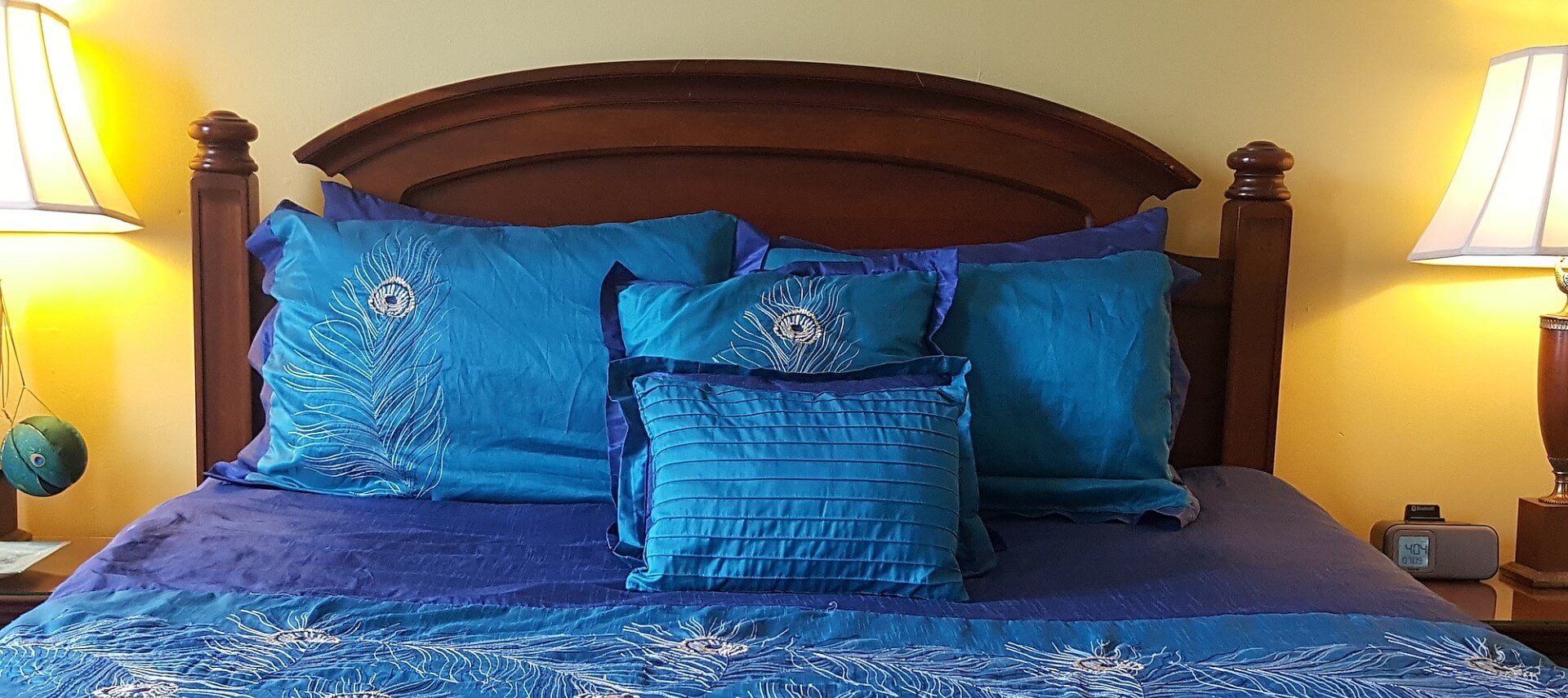 Cherry queen bed made up in peacock blue spread and shams with matching nightstands and lamps.
