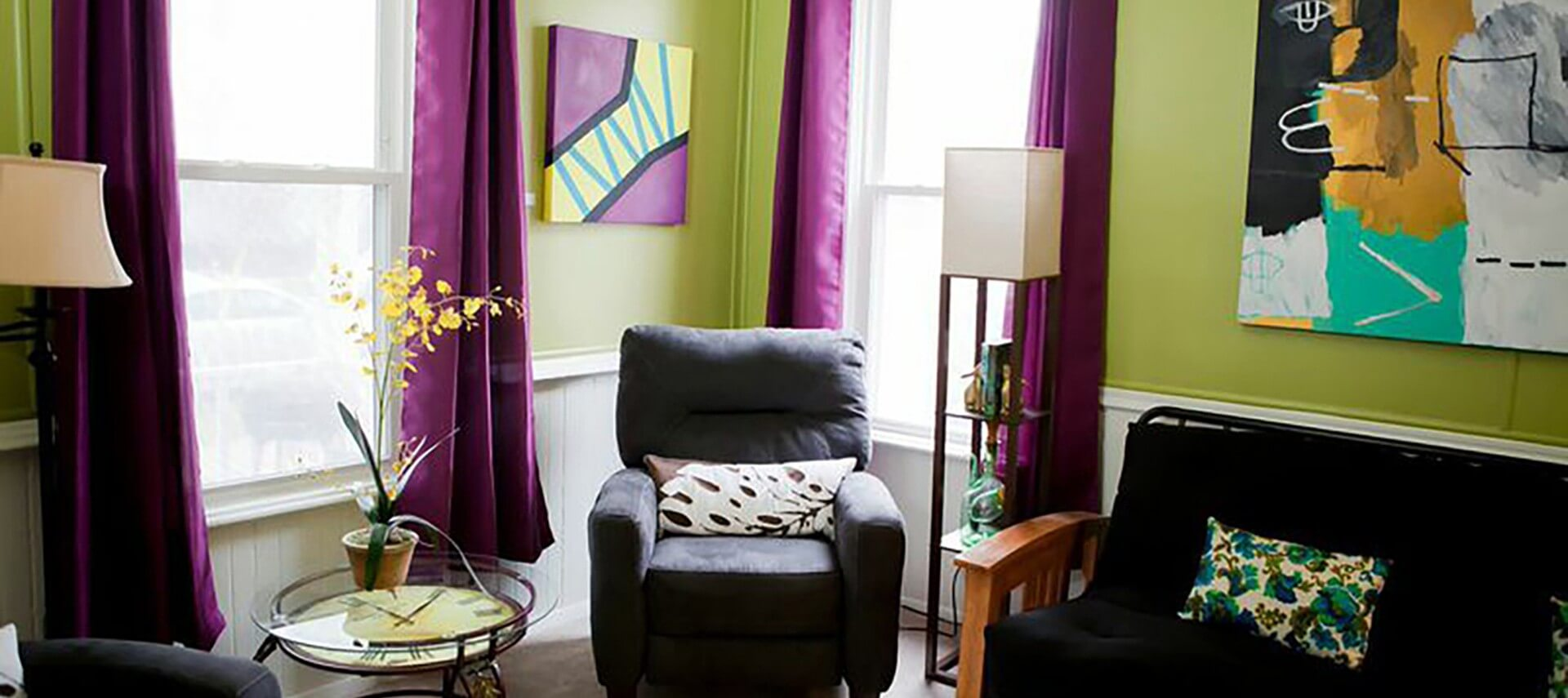 Room with lime green walls, purple drapes holds two upholstered chairs and a futon.