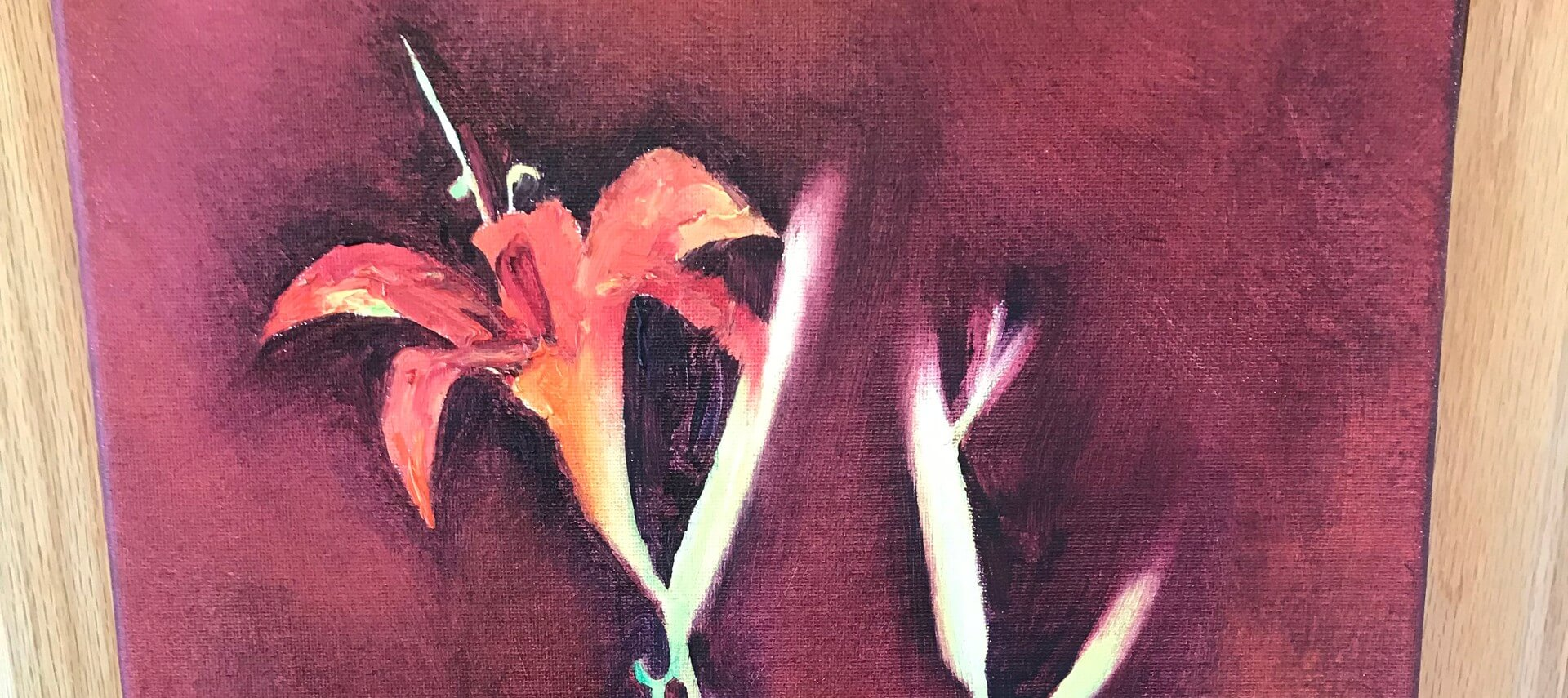 Painting of two red Irises on a burgindy background with a wooden frame.