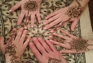 Picture of four hands with henna designs