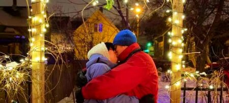 two people dressed in snow clothes kissing outside under the mistletoe